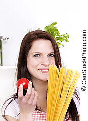 portrait of a happy young woman holding spaghetti and tomato