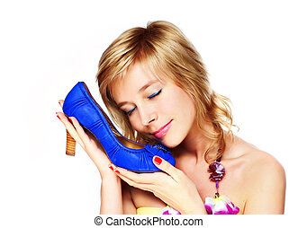 Portrait of a happy young woman holding a blue shoe at a store