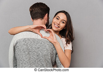 Portrait of a happy young woman hugging her boyfriend
