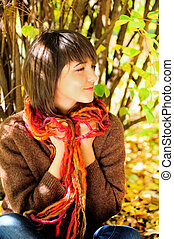 Portrait of a happy young woman in autumn park.