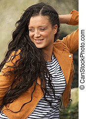 Portrait of a happy young woman smiling outdoors