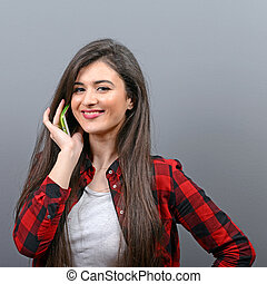 Portrait of a happy young woman talking on a cellphone against gray background