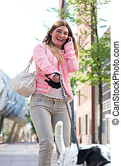 Portrait of a happy young woman walking her dog in the city and talking on the phone