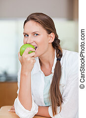 Portrait of a healthy woman eating an apple