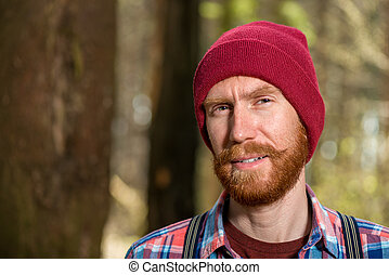 portrait of a hipster with a red beard close-up in the forest