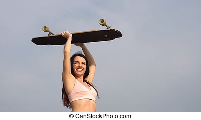 Portrait of a hipster young girl smiling with a longboard....
