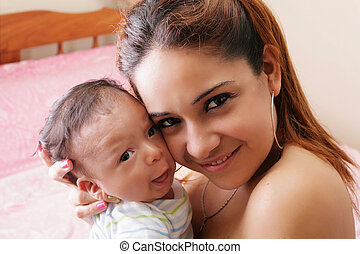 Portrait of a hispanic happy young mother holding a baby