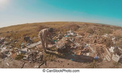 portrait of a homeless man in a dump with walking goes...