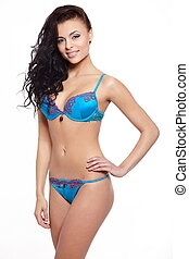 Portrait of a hot young smiling female fashion model posing in blue lingerie against white background