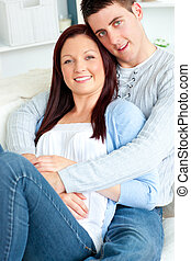Portrait of a hugging couple sitting on a sofa in the living-room at home