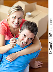 portrait of a joyful couple in their new house with woman showing the key to the camera