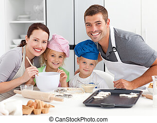 Portrait of a joyful family cooking littles cakes in the...