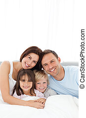 Portrait of a joyful family sitting on the bed