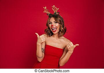 Portrait of a joyful happy girl wearing christmas deer...