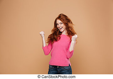 Portrait of a joyful satisfied redhead girl celebrating...