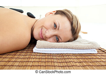 Portrait of a joyful woman lying on a massage table with hot stones in a health spa