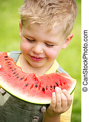 Portrait of a kid eating a slice of watermelon