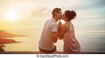 Portrait of a kissing couple watchnig a sunset