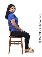 portrait of a latin woman sitting on a chair in white background,side view and looking at camera