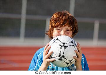 laughing boy hidden behind soccer ball - portrait of a...