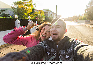 Portrait of a laughing cheerful couple holding keys to their new house. New home owners concept