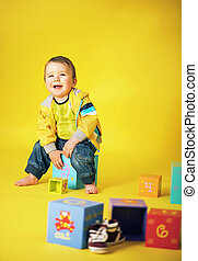 Portrait of a laughing little boy with a bunch of toys