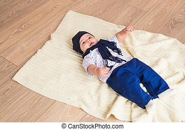 Portrait of a little adorable newborn infant baby boy lying on back on blanket