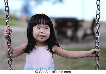 Portrait of a little asian girl in swing