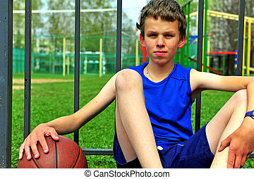 Portrait of a little basketball player sitting on the court