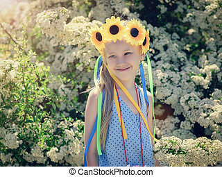 Portrait of a little beautiful girls in the sunshine with braids of colored material.