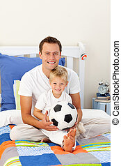 Portrait of a little boy and his father playing with a soccer ball sitting on bed