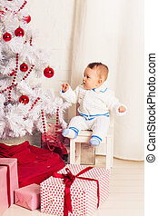 Portrait of a little boy at home near the Christmas tree.