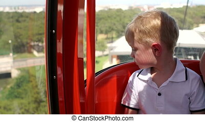 Portrait of a little boy in a cable car cabin that rises up a high mountain.