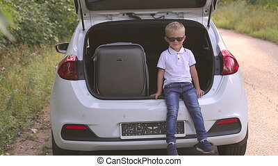 Portrait of a little boy in sunglasses in the trunk of a car next to a suitcase.