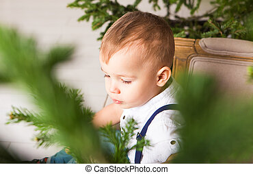 Portrait of a little boy near the Christmas tree.