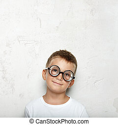 Portrait of a little boy on the concrete background and wearing glasses