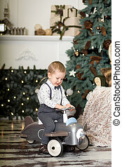 Portrait of a little boy sitting on a vintage toy airplane near a Christmas tree. Christmas decorations. The boy rejoices at his Christmas present. Merry Christmas and happy New Year 2020