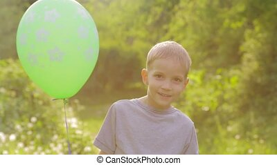 Portrait of a little boy smiling to the camera with a balloon