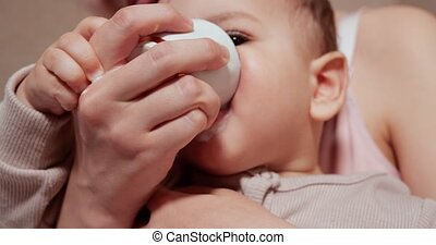 Portrait of a little boy who sits in his mother's arms. Happy child drinks milk or dairy product from a cup. Proper and natural nutrition for children