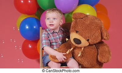 Portrait of a little boy with a toy bear.