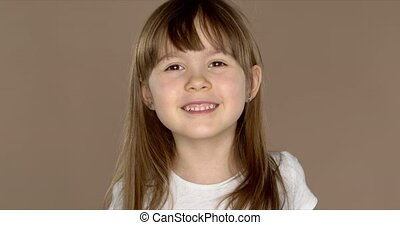 Portrait of a little cute 7 year old girl in a white tshirt...