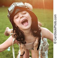 Portrait of a little flying pilot-girl having fun