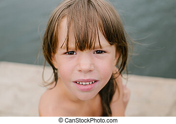 Portrait of a little girl at the beach on hot summer day