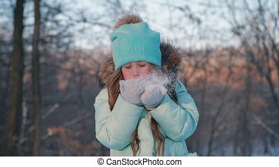 portrait of a little girl blowing on the snow