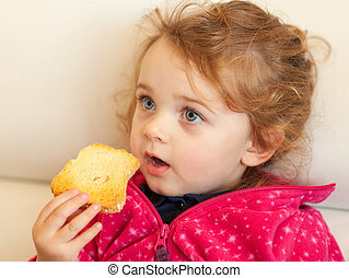 Portrait of a little girl eating a rusk