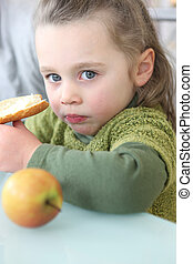 Portrait of a little girl eating a sandwich