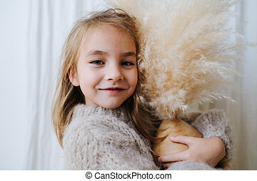 Portrait of a little girl hugging coconut vase with cereal bouquet in it.