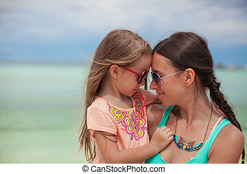 Portrait of a little girl hugging with her mother on the beach