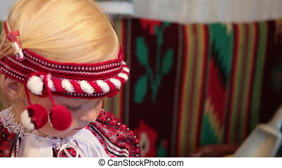 Portrait of a little girl in an old Ukrainian vyshyvanka costume, smiling.