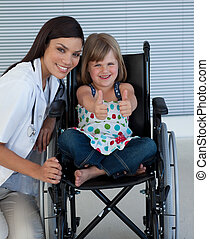 Portrait of a little girl on a wheelchair with her doctor
